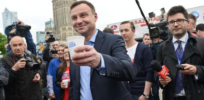 Kandydat na prezydenta Andrzej Duda (C) rozdaje kawę przed wejściem na stację metra Centrum w Warszawie, 11 bm. Duda, który wg sondaży wygrał I turę wyborów, w drugiej turze 24 bm. zmierzy się z Bronisławem Komorowskim. (zuz) PAP/Marcin Obara