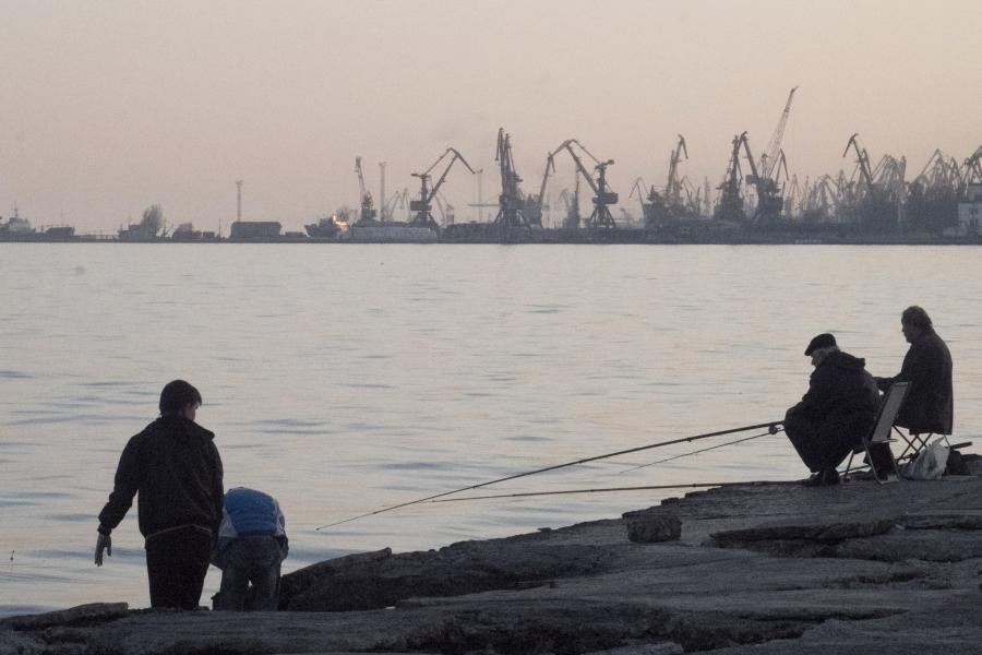 Żurawie portowe w Mariupolu, jednym z największych portów handlowych Ukrainy. Wędkarze łowią ryby z nabrzeża przy morzu Azowskim, w poniedziałek, 24 marca 2014. Fot: Vincent Mundy/Bloomberg